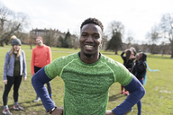 Portrait smiling, confident male runner in sunny park - CAIF21144