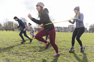 Women exercising, doing team building exercise in park - CAIF21150