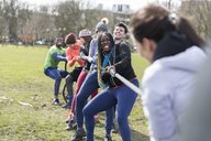 Determined team pulling rope in tug-of-war in park - CAIF21153