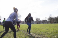 Woman cheering friend doing speed ladder drill in sunny park - CAIF21159