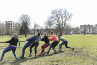 Determined team pulling rope in tug-of-war in park - CAIF21162