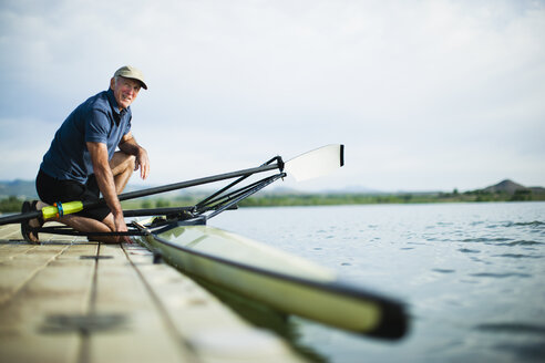 A middle-aged man on a jetty preparing a rowing boat for an outing. - MINF00038