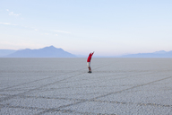 A man wth arms raised, in the dawn light in Black Rock Desert, Nevada. - MINF00071