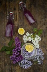 Two glass bottles of homemade lilac sirup and ingredients on wood - LVF07297