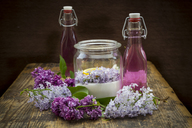 Glass bottles of homemade lilac sirup and ingredients in glass - LVF07303