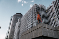 Beautiful woman wearing dungarees, standing on ledge in front of modern high-rise building - KKAF01220