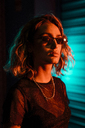 Stylish young woman at night in front of roller shutter, wearing sunglasses - KKAF01241