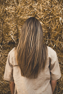 Beautiful young woman standing in front of hay bales, rear view - ACPF00130