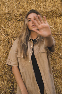 Young woman standing in front of hay bales making rejecting hand gesture, portrait - ACPF00133