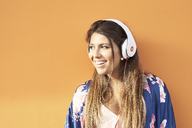Portrait of smiling young woman with headphones in front of orange background - JNDF00009