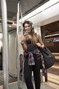 Portrait of smiling woman with guitar backpack and headphones looking at cell phone in underground train - JNDF00012