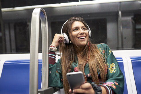 Portrait of happy woman listening music with headphones and smartphone in underground train - JNDF00015