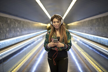Portrait of woman with headphones looking at smartphone in underground station - JNDF00018