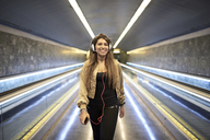 Portrait of smiling woman with headphones and smartphone in underground station - JNDF00021