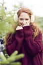 Portrait of redheaded young woman wearing ear muff and knit pullover - ABIF00699