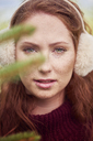 Portrait of redheaded young woman with freckles wearing ear muff - ABIF00702