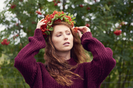 Portrait of redheaded young woman wearing wreath of rowanberries - ABIF00714