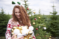 Smiling redheaded young woman with wire basket of Christmas baubles outdoors - ABIF00717