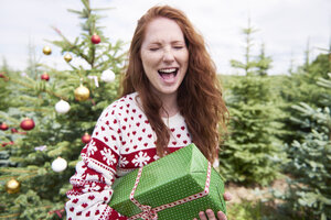 Portrait of redheaded woman with Christmas present crying of joy - ABIF00720