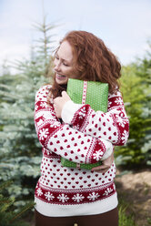Happy redheaded young woman embracing Christmas present outdoors - ABIF00723