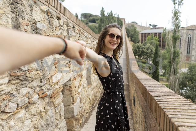 Spain, Girona, smiling woman holding man's hand walking along stone wall - AFVF00811