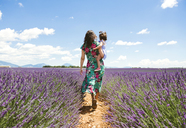 France, Provence, Valensole plateau, Mother and daughter walking among lavender fields in the summer - GEMF02119