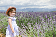 France, Provence, Valensole plateau, Happy toddler girl standing in purple lavender fields in the summer - GEMF02140