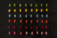 Arrangement of colorful candies on black ground - AFVF00824