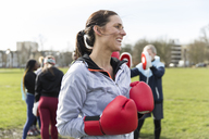 Smiling, confident woman boxing in park - CAIF21180