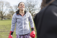 Smiling woman boxing in park - CAIF21183
