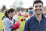 Portrait smiling, confident young man boxing in park - CAIF21192