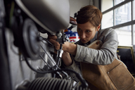 Woman working in repair workshop - RBF06424