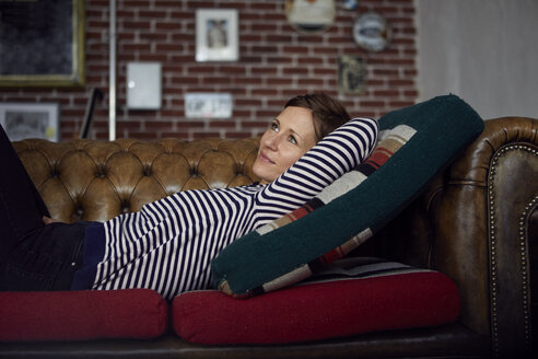 Woman on sofa relaxing at home, daydreaming - RBF06448