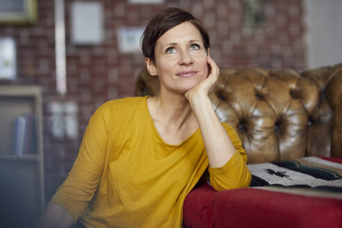 Attractive woman sitting at home with hand on chin - RBF06451