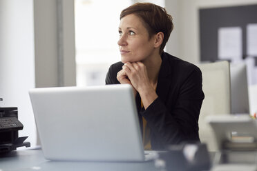 Businesswoman sitting in office, using laptop - RBF06457