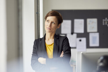 Attractive businesswoman standing in office with arms crossed - RBF06460
