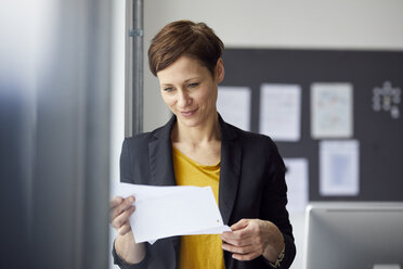 Attractive businesswoman standing in office, readiing document - RBF06463