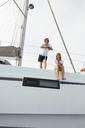Mature couple making holidays, sailing on a catamaran - EBSF02575