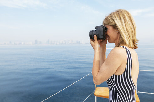 Mature woman on sailing trip photographing skyline of Barcelona - EBSF02578