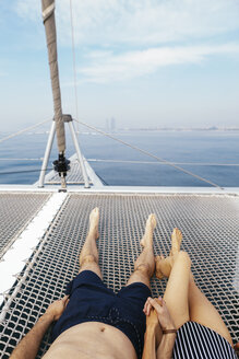 Mature couple on a sailing trip lying on trampoline, relaxing - EBSF02581
