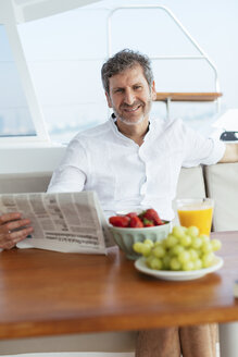 Mature man on a sailing trip having a healthy breakfast, reading newspaper - EBSF02590