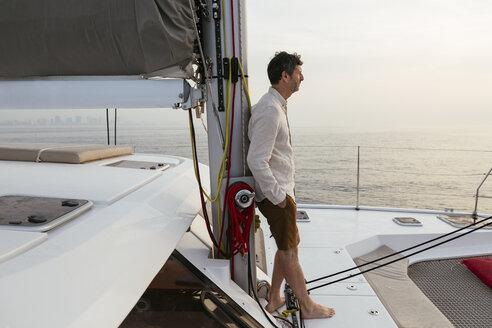 Marure man on catamaran, looking ta view - EBSF02605
