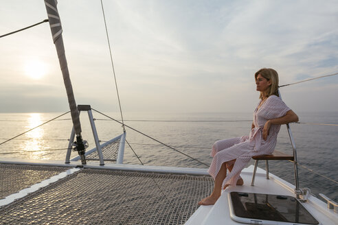 Mature woman on catamaran, watching sunset - EBSF02608
