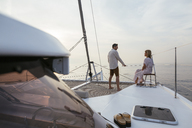 Mature couple standing on catamaran trampoline, enjoying their sailing trip - EBSF02611
