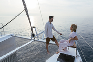 Mature couple standing on catamaran trampoline, enjoying their sailing trip - EBSF02614