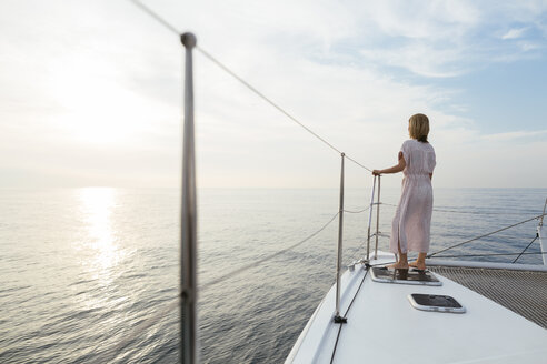 Mature woman standing on catamaran, watching sunset - EBSF02626