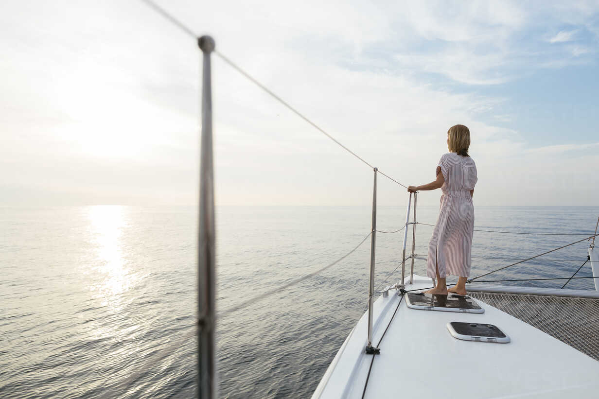 Mature woman standing on catamaran, watching sunset - EBSF02626 - Bonninstudio/Westend61