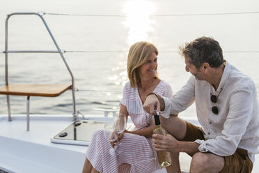 Mature couple drinking wine at sunset on a sailing boat - EBSF02629