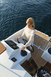 Mature woman navigating catamaran on a sailing trip - EBSF02641