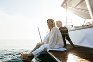 Mature couple sitting on jetty, relaxing at the sea - EBSF02644